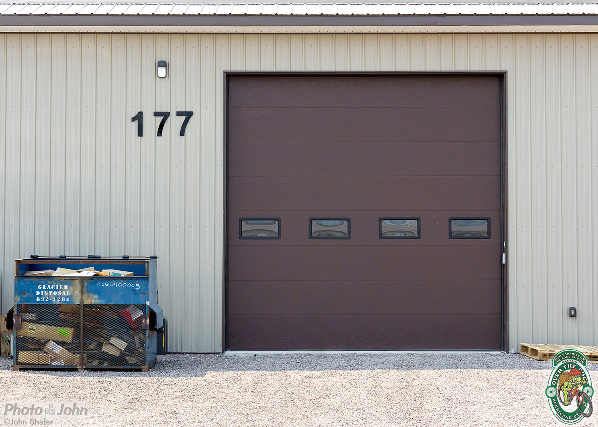 A beige metal warehouse building with a brown rollup door.