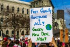 """At a rally, a demonstrator holds a sign up reading, """"Free quality health care for all! Green New Deal NOW!"""""""