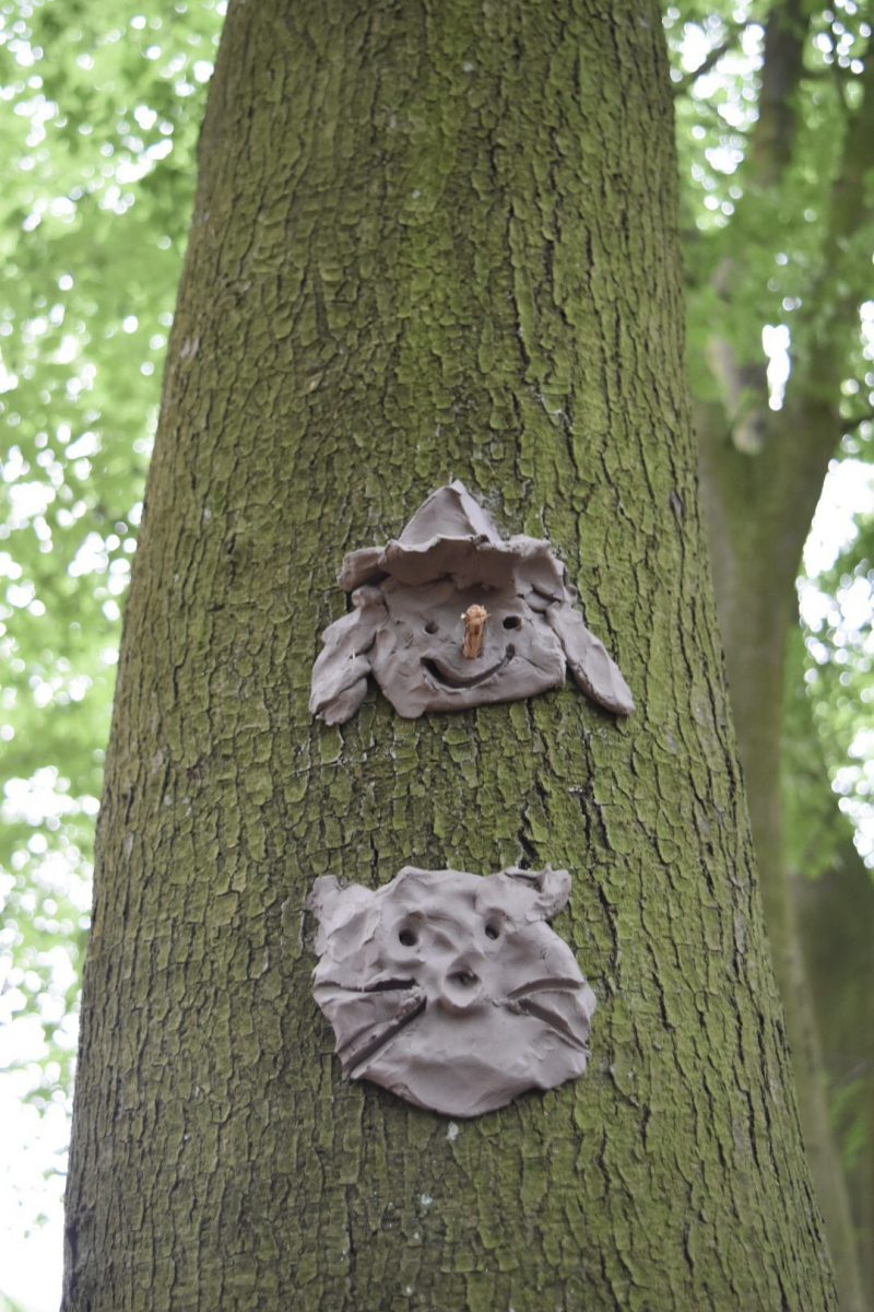 clay face and clay sculptures on a tree trunk for an party with a festival theme idea