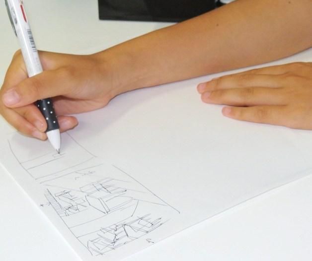 一時保護所の生活について、絵を描いて説明する少女=7月、東京都内
