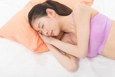 寝ながら育乳している女性