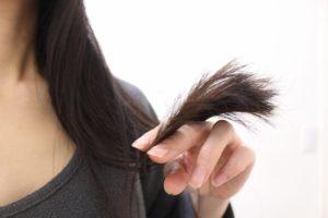 痛んでいる毛先を気にしている女性の画像