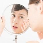 ニキビ跡を気にして鏡を覗き込む女性の画像