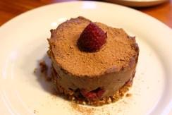 Schoko-Creme-Törtchen in Rohkostqualität mit Avocadocreme, Kakao und Nüssen, mit Datteln gesüßt und Himbeeren verfeinert.