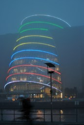A cyclist whizzes by... the multi coloured Convention Center in the mist...