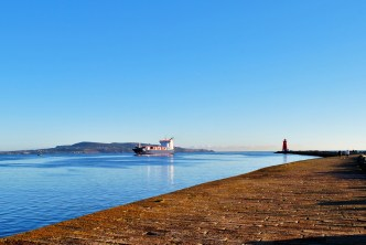 Ferry entering the Liffey Channel, Dublin, Ireland. The Poolbeg Lighthouse and Howth in the distance...