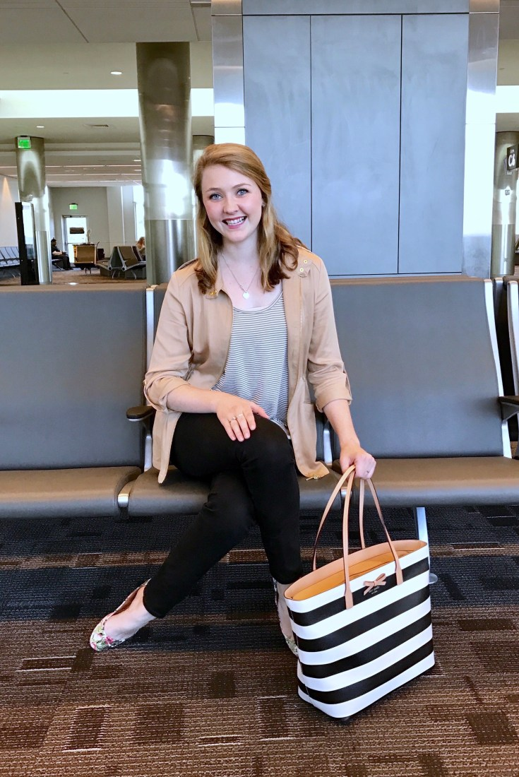 Bonnie sits on a chair in the airport. Her travel outfit is made up of an olive green and white striped tank with a camel colored jacket, black jeans, floral patterned ballet flats, and is holding a back and white Kate Spade tote bag.