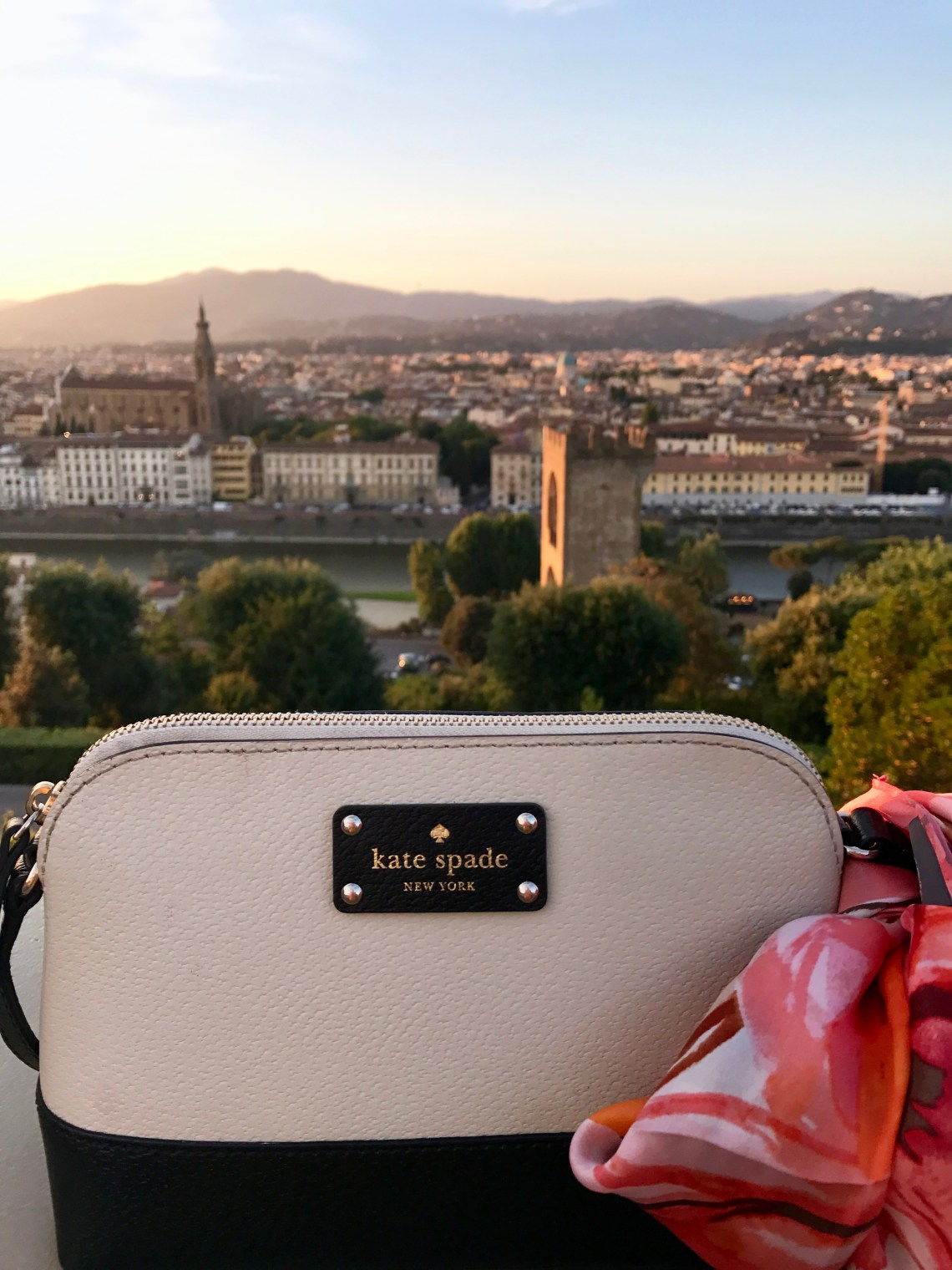 black and cream Kate Spade purse with silk scarf tied to the strap against the Florence sunset