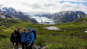 Kolme henkilöä Alaskassa jäätikön edustalla