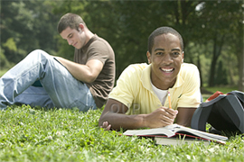 Teenager reading from a book on the grass and smiling