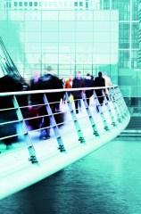 Businessmen and women walking over a modern city bridge