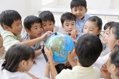 Group of children crowding around a model globe