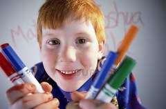 Smiling child holding colored pens