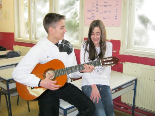 Student playing guitar with another student singing