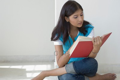 Asian girl sitting on the floor reading