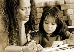 Teacher helping young girl to read