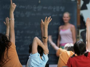 Children in class raising their hands