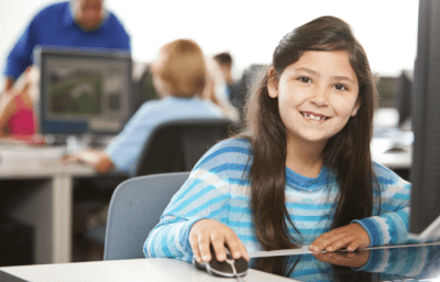 Girl sat at computer smiling