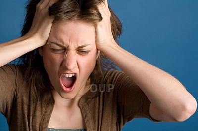 Young stressed woman holding her head and yelling.
