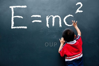 Young boy writing equation on chalkboard