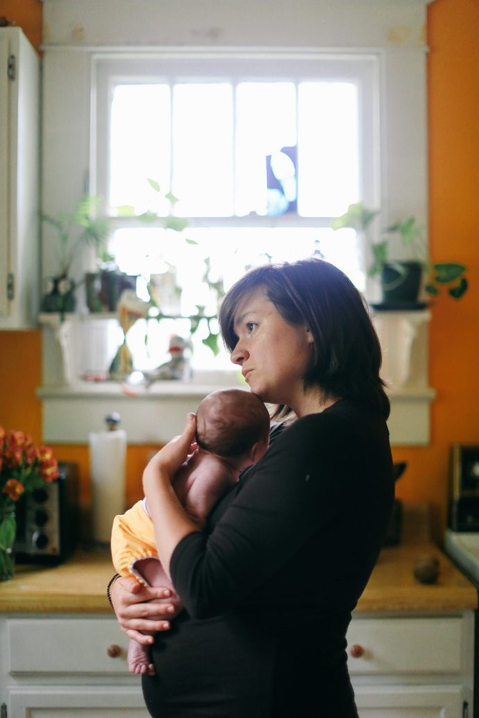 Audrey cuddles with her sweet new born Ezra in the kitchen