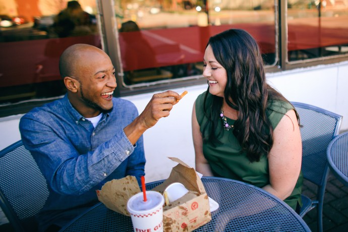 Sweet couple eating fries at their engagement shoot in Chattanooga