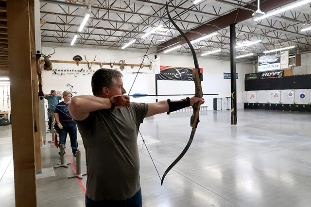 Chris with an arrow drawn, aiming down range.