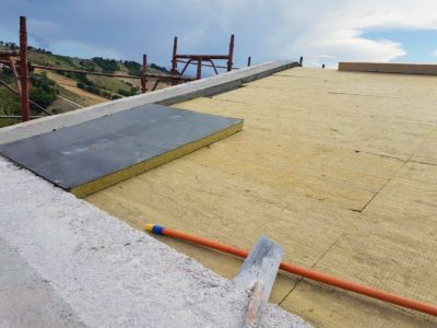 Adding the Next Layer to a roof  of a new house being built in Le Marche, Italy