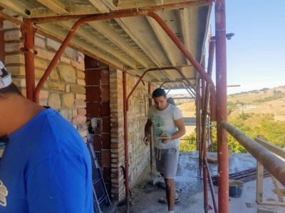 Carrying the Stucco for an exterior stone wall on a new house in Le Marche