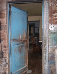 Worn turquoise door half open
