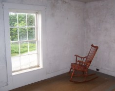 Rocking chair in white-walled parlor with paned window