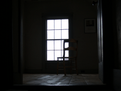 Chair silhouetted against paned attic window