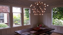 Dining room with white painted paneling and modern light fixture