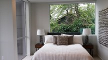 Bed in front of window with leafy view