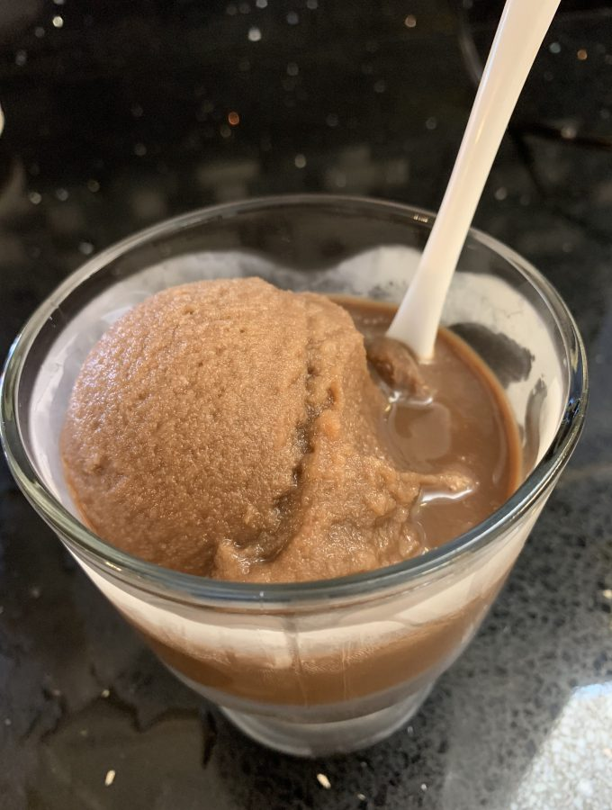 Chocolate water ice in a cone shaped glass bowl with a metal spoon.
