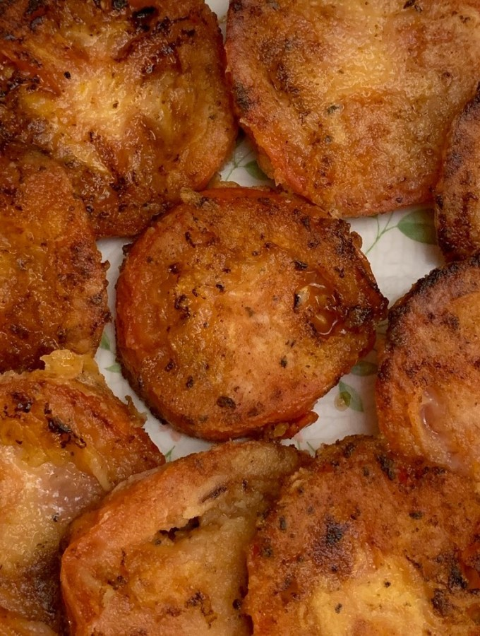 Sliced tomatoes fried with flour, salt and pepper on a plate.