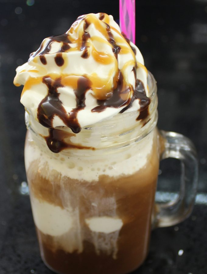 Coffee drink with vanilla ice cream, whipped cream, chocolate syrup, and caramel sauce in a mug with a pink straw
