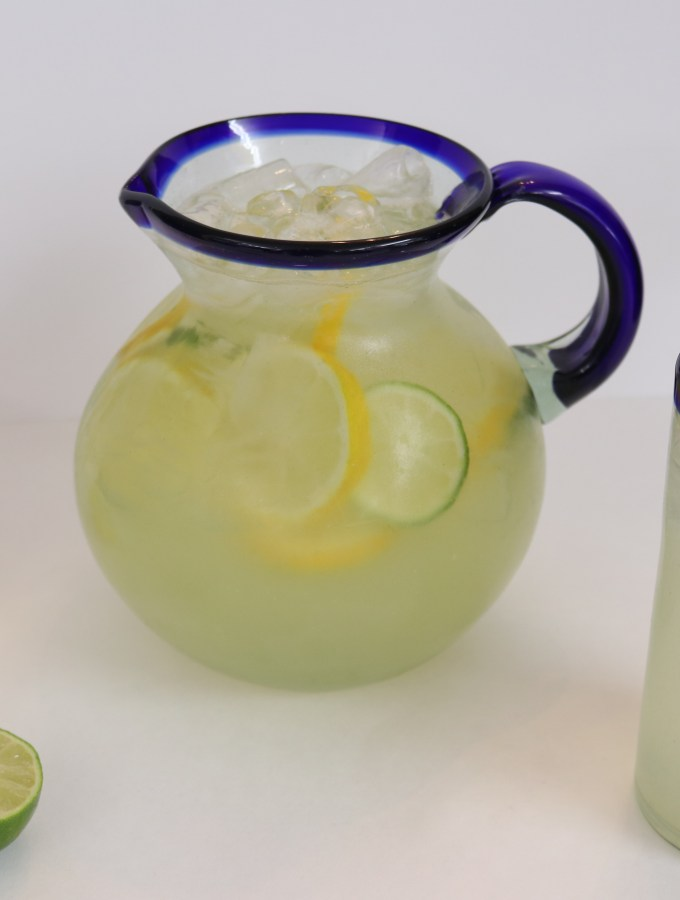 A pitcher of lemon-limeade with a tall glass of it and lemon and lime halves next to the pitcher