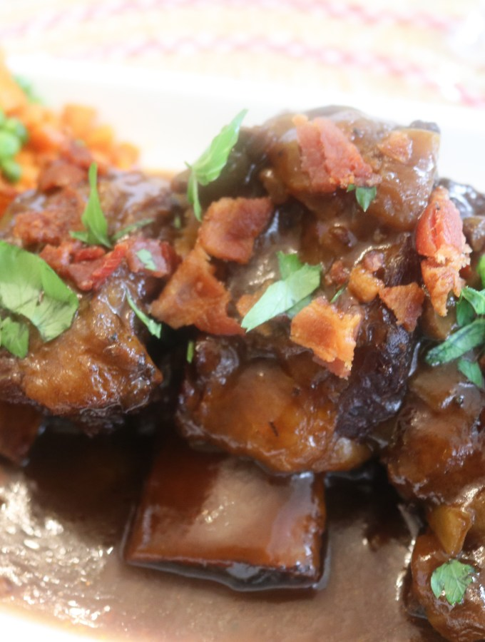 Zoomed up Beef Short ribs topped with gravy, bacon , and parsley served with potatoes, peas and carrots, and a popover