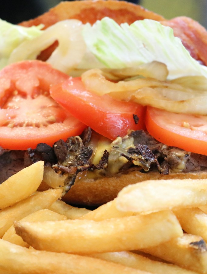 Thin steak sandwich meat on a hoagie roll with tomatoes, cheese, and lettuce. It has a side of french fries with it