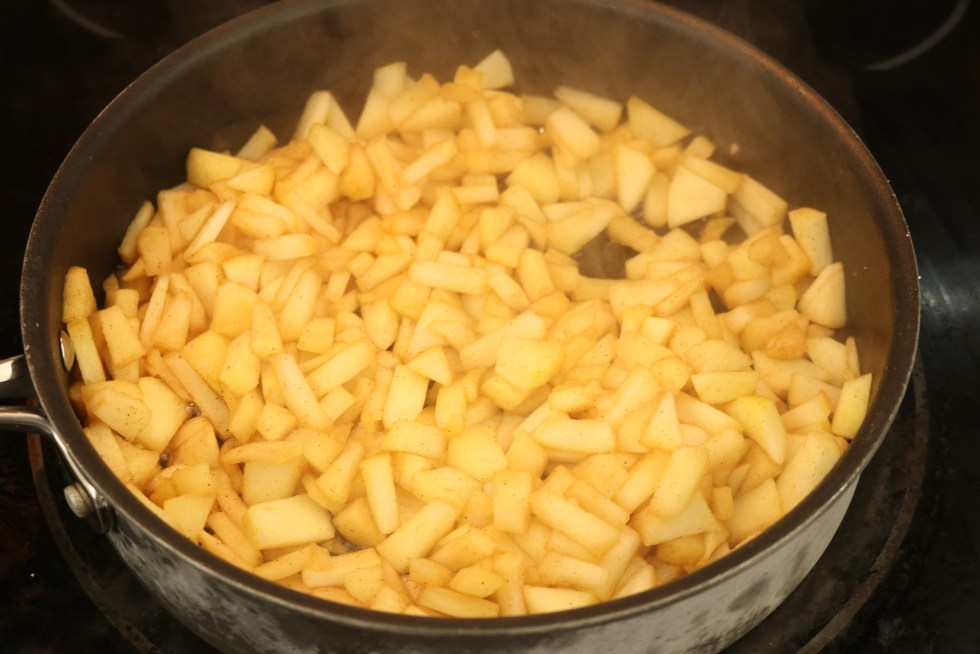 Chopped apples cooked in a black skillet with sugar and cinnamon