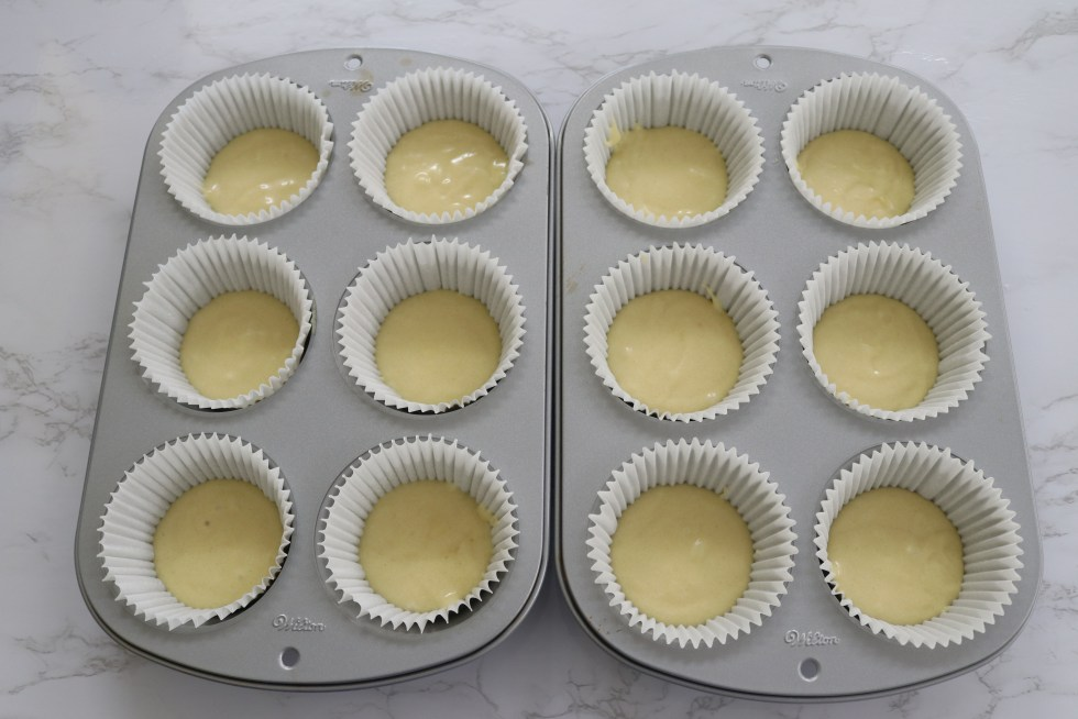 Silver muffin pans with white liners filled half way