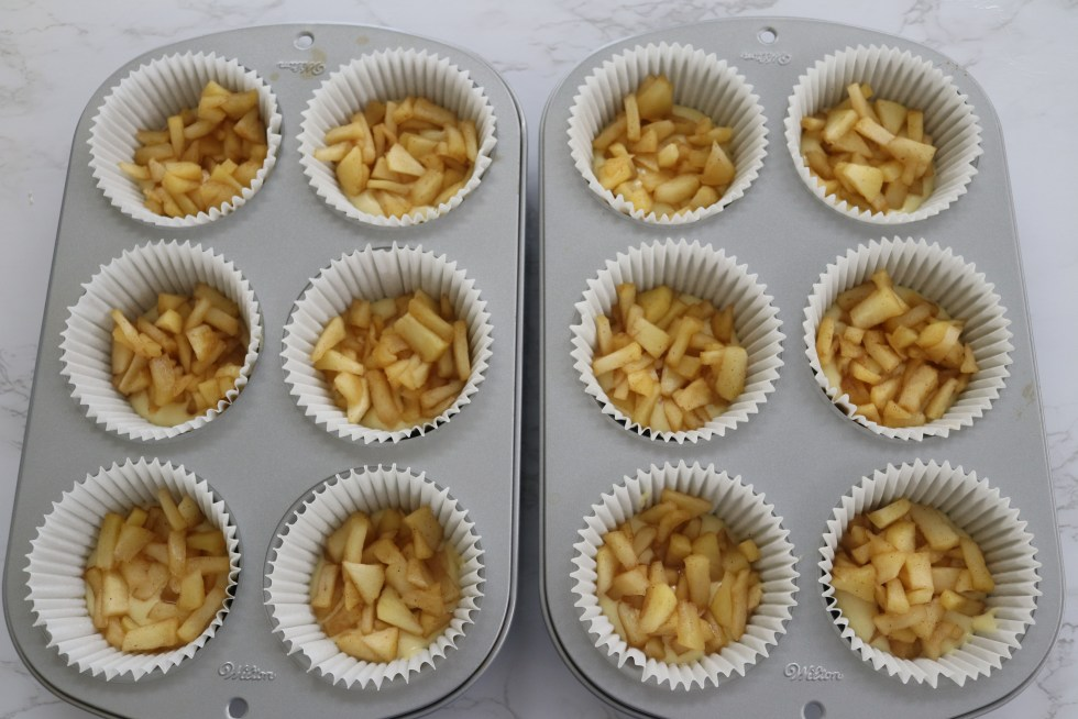 Silver muffin pans filled with chopped apples