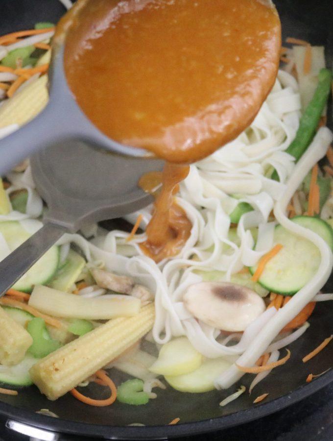 adding the stir fry sauce to a stir fry