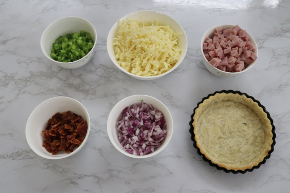 Small white bowls filled with cheese, green pepper, red onions, chopped ham, pieces of bacon, and a tart pan