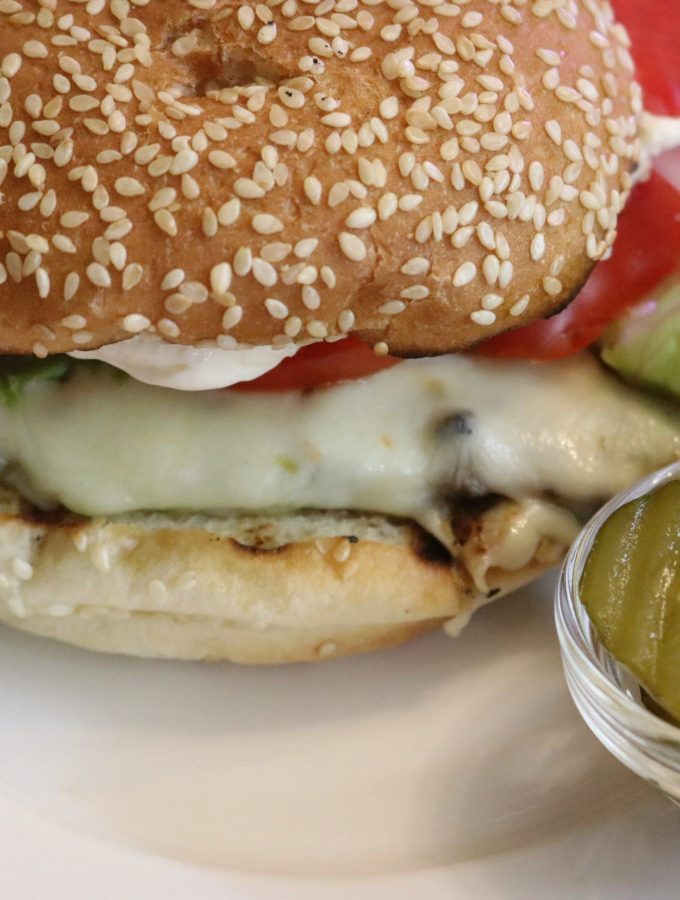 Grilled chicken sandwich on sesame bun with lettuce, onion, tomatoes, potato chips and pickles on a white plate