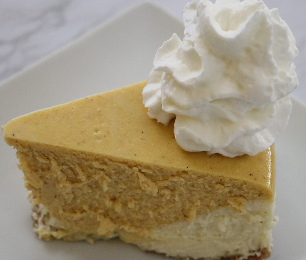 Pumpkn vanilla cheesecake on a white plate with whipped cream