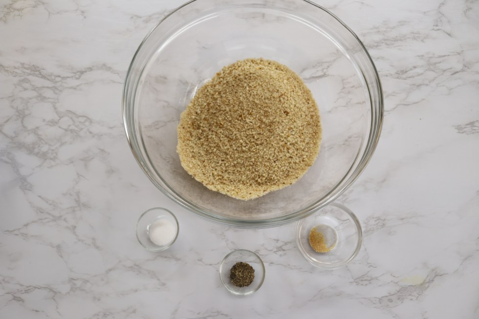 Large bowl filled with breadcrumbs and 3 small bowls with salt, pepper, and garlic powder