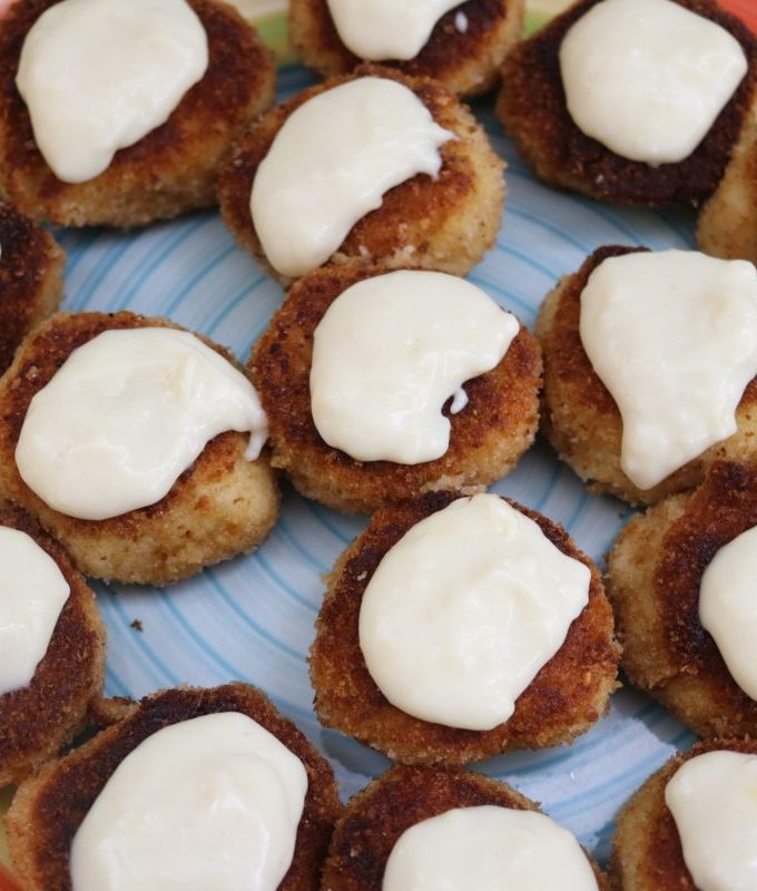 Appetize chicken croquettes topped with cream sauce on a yellow and orange plate