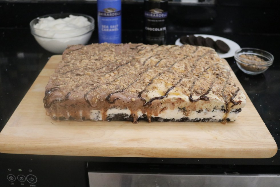 Rectangular sheet cake of ice cream covered with syrup and toffee sprinkles